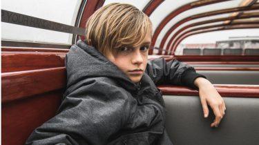 kind in de puberteit op een boot kijkt chagrijnig
