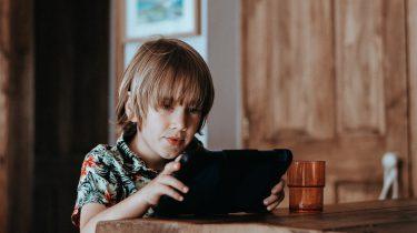 Jongen op een tablet die niet weet wat verantwoord schermgebruik is