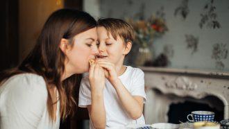 Jongetje die zijn moeder iets laat proeven aan tafel