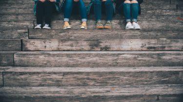 Tieners chillen samen op een trap: een puber kan tijdens de puberteit wel wat advies gebruiken